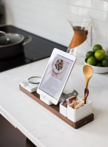 Photo of an ipad, propped up in a kitchen with spoons and limes nearby. A recipe is visible on the ipad's screen.